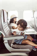 Two little girls flying on plane