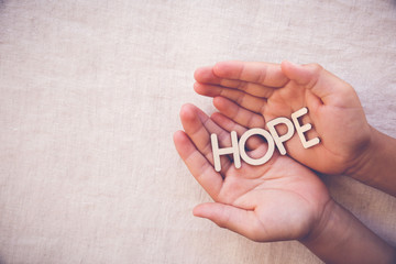 HOPE wooden word on praying hands on toing copy space background