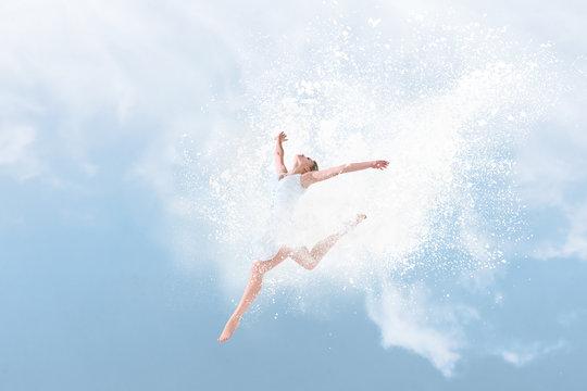 Beautiful ballet dancer jumping inside cloud of powder
