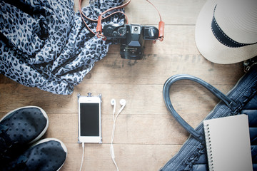 Flat lay photography with cellphone, travel accessories, essenti