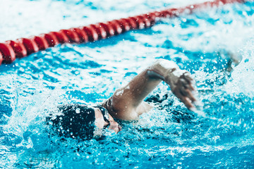 Front crawl swimmer . Female swimming in the indoor pool