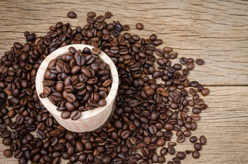 Coffee beans set up on wooden cask and rustic background