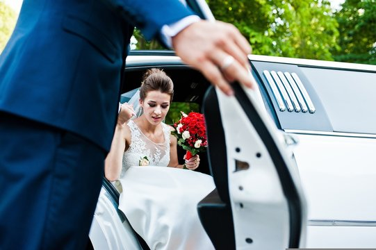 Groom open door of limousine and take hand to bride