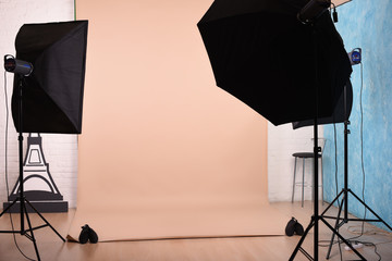 Empty photo studio with lighting equipment and paper background ready for photoshoot.