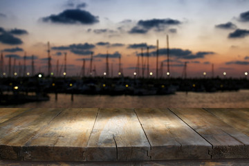 image of wooden table in front of abstract blurred yachts