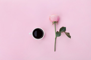 Pink rose flower and cup of coffee on pastel background top view. Flat lay style.