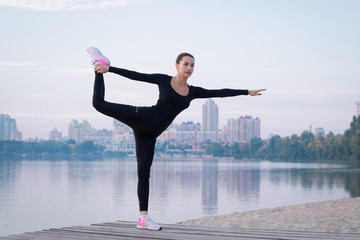 Young woman exercises on pier during morning fitness workout