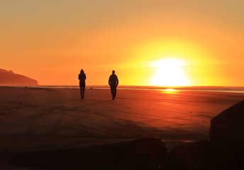 two people walking into sunset at beach