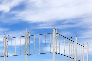 Vintage metal fence and a blue cloudy sky