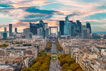 La Defense Financial District Paris France in autumn. Traffic on Champs-Elysees with orange and yellow trees aside. Modern vs. Old architecture. Sunset bright sky.