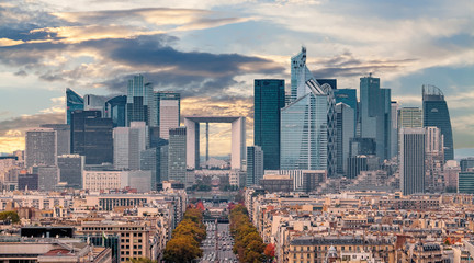 La Defense Financial District Paris France in autumn. Traffic on Champs-Elysees with orange and yellow trees aside. Modern vs. Old architecture. Sunset sky with clouds.