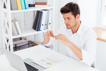 Handsome young businessman taking photo of documents with smartphone