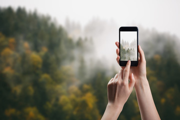 Taking picture of fog over fir trees in mountains