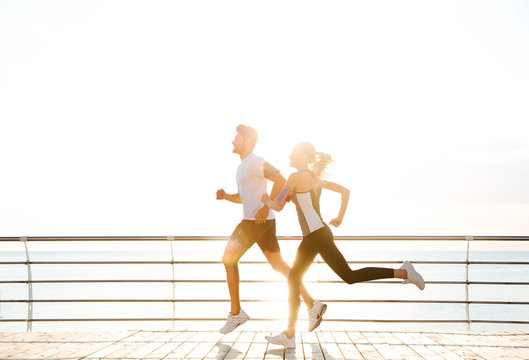 Young sporty couple running over wooden pier