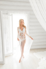 A young bride's wedding morning, she's posing walking, looking aside, bright light from the window beside her. Boudoir. Morning of the bride. Wedding.
