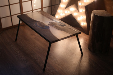 Wood and epoxy table with star lamp in wooden interior