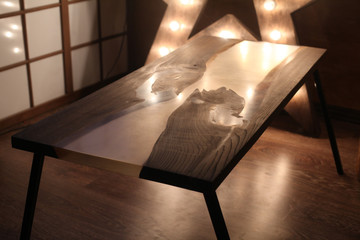 Wood and epoxy table with star lamp in wooden int
