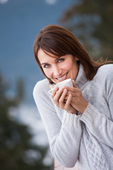 femme souriante qui boit un café sur une terrasse en hiver