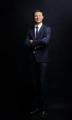 Handsome business man smiling on black background