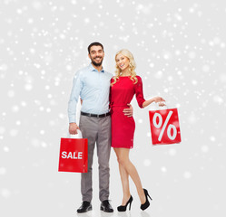 happy couple with red shopping bags over snow