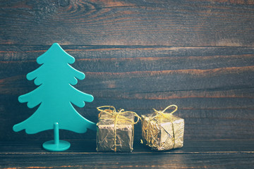 Christmas gifts. Decorative New Year tree with a festive boxes in gold shiny paper on a wooden background in vintage color. Holidays gift background