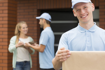 Happy courier holding a package for woman