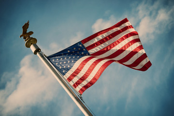 American flag on pole waving in the wind against blue sky background