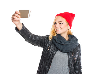 Girl in hat and scarf makes selfie. On white, isolated background.