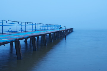 Misty morning on the lake. Old abandoned pier goes into the fog