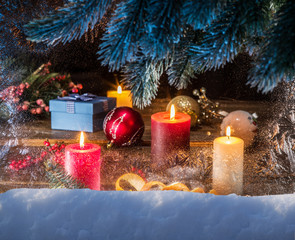 Gift boxes, candle lights and frozen window. Christmas backgroun