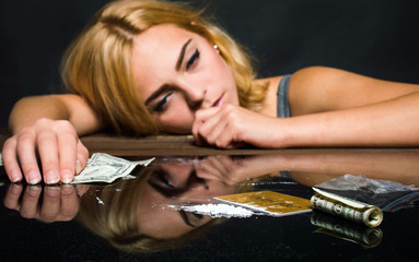 Addict lies on a table in front of a dose. On a black background.