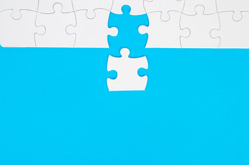 White, disassembled puzzle. On a blue background.Top view. Flat lay.