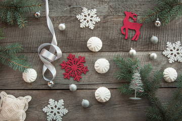 Christmas decor laid out on a wooden surface. Fir branches, silver ribbon and ball, white marshmallow, snowflakes, toy red deer and decor around. Top view and copyspace. Flat lay.