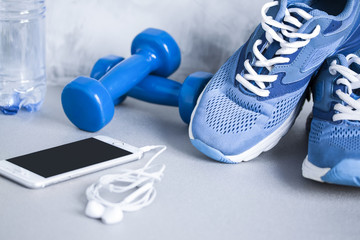 Sport shoes, dumbbells, mobile phone, earphones and bottle of wa