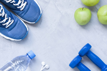 Flat lay sport shoes, dumbbells, earphones, apples, bottle of wa