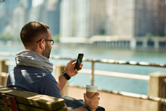 Enjoying city life. Handsome young man  having coffee to go. New York city in background