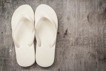 Flip-flops cream color on a wooden background.