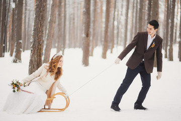 Winter wedding. Beautiful young couple in the woods. groom pulls