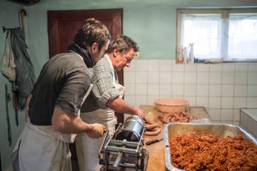 Men making sausages the traditional way using sausage filler.