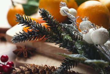 Top view of desktop with tangerines and leaves in Christmas decor.