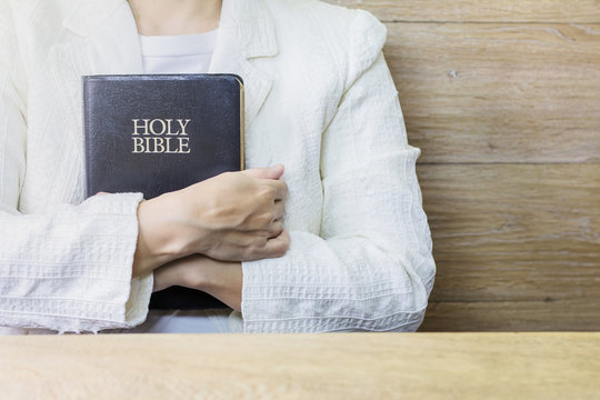 a woman hands holding the holy bible over wooden table