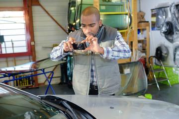 Mechanic taking photograph of car
