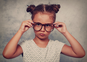 Serious angry kid girl with modern hair style in fashion glasses