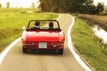 Classic red convertible car traveling in the countryside at sunset Wall mural