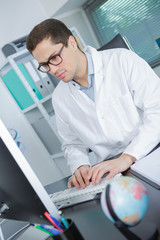 happy male doctor working at office