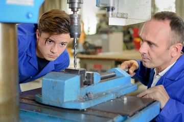 Two men using bench drill