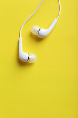 White headphones on a yellow paper background
