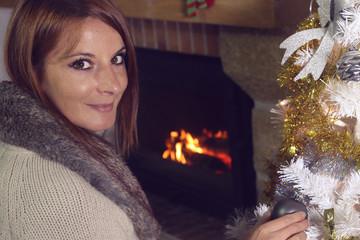 Portrait d' une femme décorant son sapin de Noël