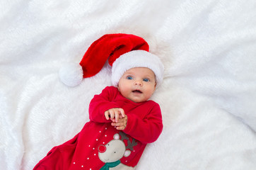 cheerful a baby girl with blue eyes in santa hat lying on a bed