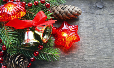 Christmas decoration with fir tree branches,red garland lights,cones and bells on old wooden background.Winter holidays,Christmas or Happy New Year concept.Copy space,selective focus.
